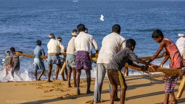 Fisherman pulling fishing net from the ocean