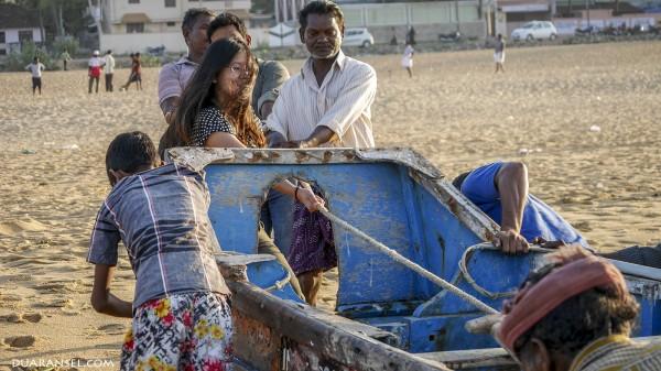 Pulling fisherman boat to the shore at Kollam Beach, India